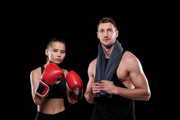 Menina desportiva com luvas de boxe vermelhas e o namorado musculoso com uma toalha, próximos um do outro