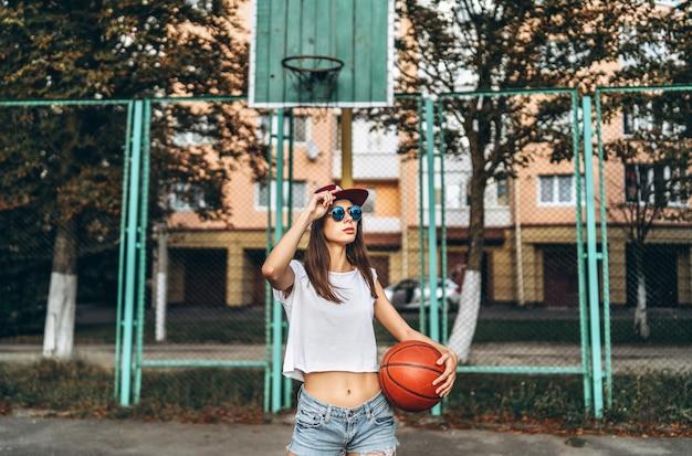 Menina desportiva consideravelmente nova com a bola do basquetebol ao ar livre.