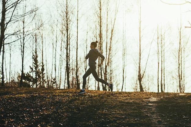 Menina desportiva correndo em uma estrada rural