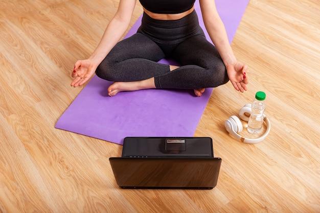 Menina desportiva irreconhecível meditando na frente de um laptop dentro de casa