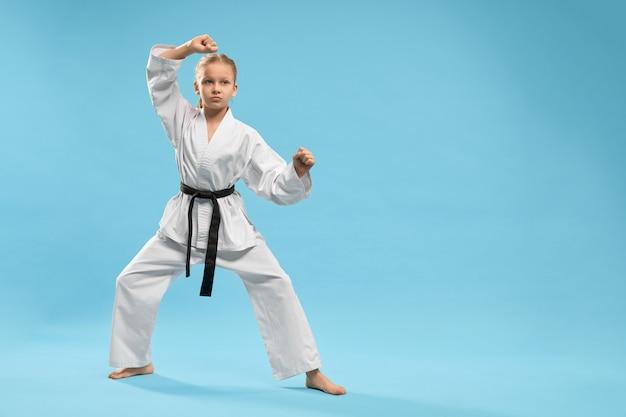 Menina desportiva que está na posição e treinando o karaté no estúdio