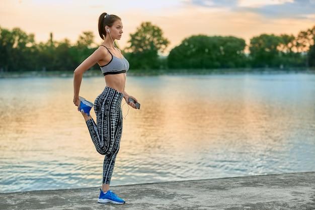 Menina desportiva que exercita no ar fresco no verão. vestindo sportwear moderno elegante.