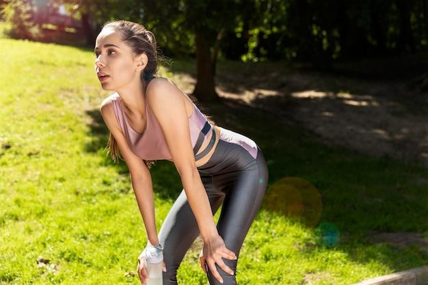 Menina desportiva tem uma pausa e bebe água durante o exercício