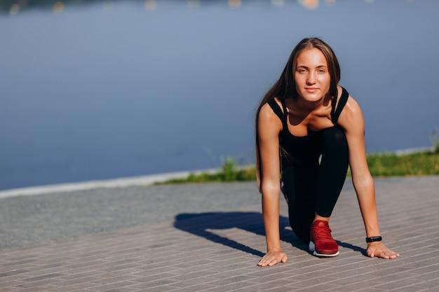 Menina desportiva warmimg ao ar livre e esticando as pernas, olhando para a câmera