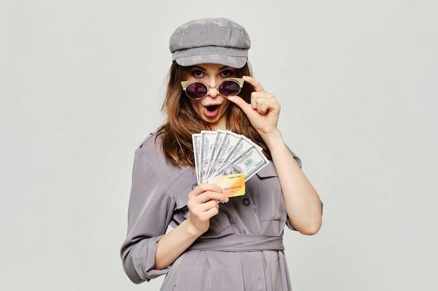 Menina detém um cartão de crédito bancário e dólares americanos como um conceito de empréstimos.