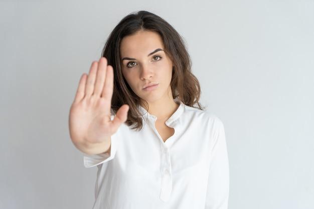 Menina determinada séria que mostra o sinal de parada.
