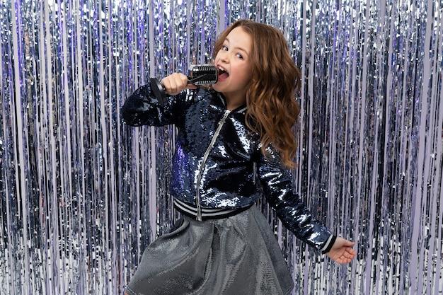 Menina divertida, alegre e elegante com um microfone nas mãos