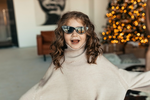 Menina divertida e adorável com cachos, suéter de malha grande e óculos escuros dançando na frente da árvore de natal