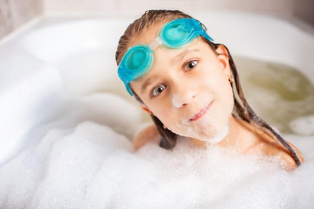 Menina divertida e positiva caucasiana usando óculos de natação