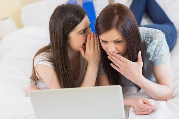 Menina dizendo um segredo para sua amiga na frente do laptop