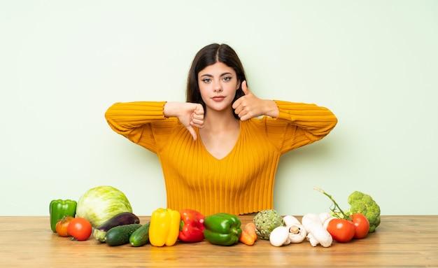 Menina do adolescente com muitos vegetais que fazem o sinal bom-ruim. indeciso entre sim ou não