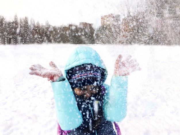 Menina do adolescente no divertimento exterior do inverno e na neve de jogo.