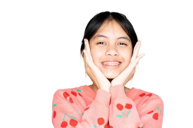 Menina do aparelho dentário sorrindo e olhando para a câmera em fundo branco, ela se sente feliz e tem boa atitude com o dentista. motive as crianças a não ter medo quando precisam ir a uma clínica odontológica.