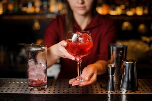 Menina do barman, segurando nas mãos um copo de cocktail vermelho