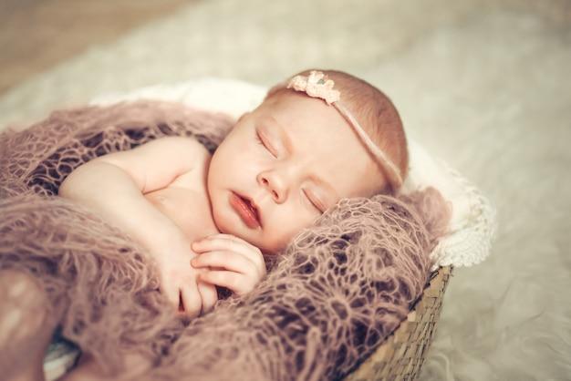 Menina do bebê recém-nascido dormindo em uma cesta.