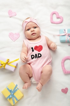 Menina do bebê recém-nascido em t-shirt com a inscrição, eu amo o pai, olhando para a câmera. dia dos namorados. vista do topo