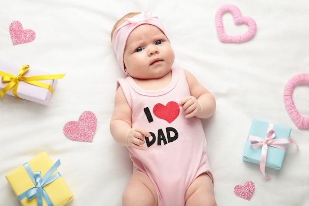 Menina do bebê recém-nascido em t-shirt com a inscrição, eu amo o pai, olhando para a câmera. dia dos namorados