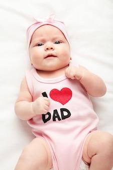 Menina do bebê recém-nascido em t-shirt com a inscrição, eu amo o pai, olhando para a câmera. vista do topo