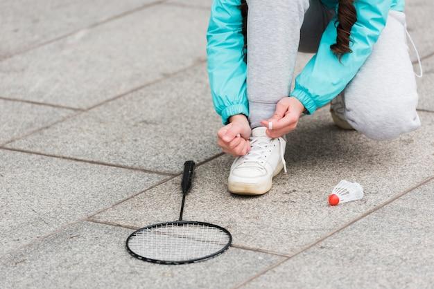Menina do close-up amarrar cadarços de sapato