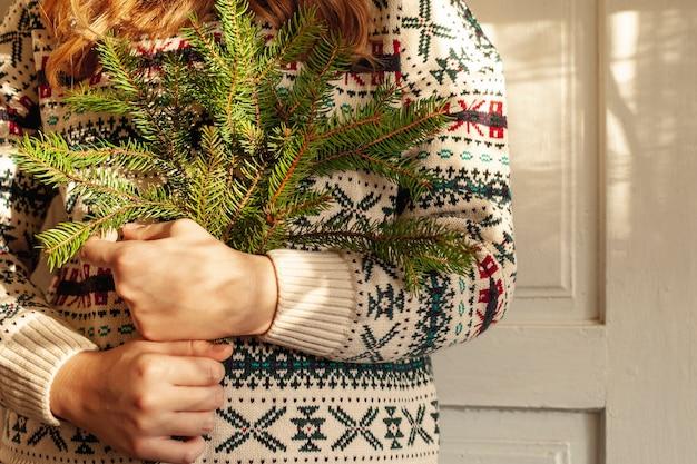 Menina do close-up com galhos bonitos da camisola e da árvore de abeto