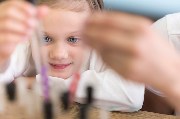 Menina do close-up com tubos de ciência