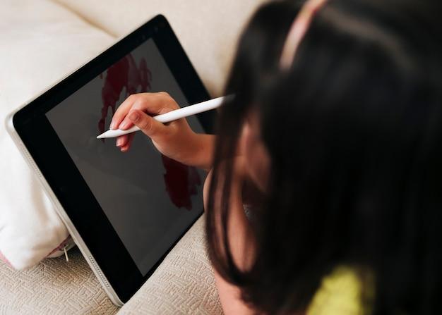 Menina do close-up de desenho em seu tablet com caneta