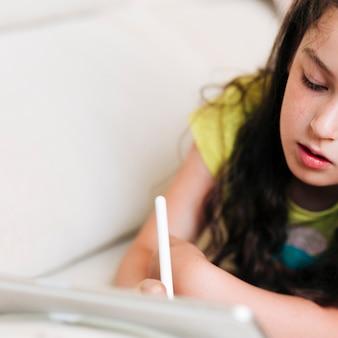 Menina do close-up de desenho em seu tablet