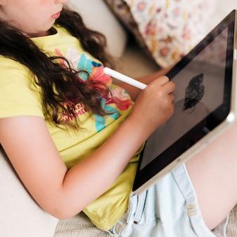 Menina do close-up de desenho em um tablet