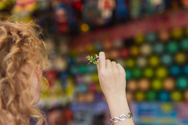 Menina do close-up que guarda a seta do dardo