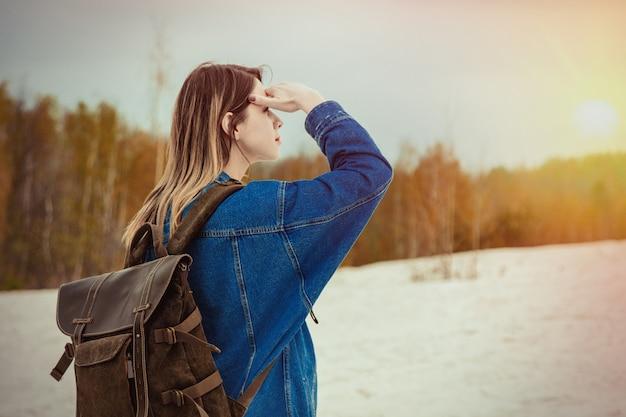 Menina do curso com a trouxa perto da floresta no tempo de mola.