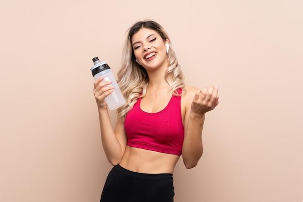 Menina do esporte adolescente com garrafa de água de esportes