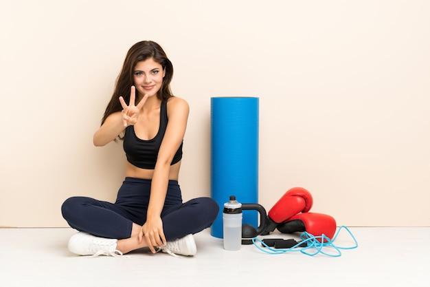 Menina do esporte adolescente sentada no chão feliz e contando com três dedos