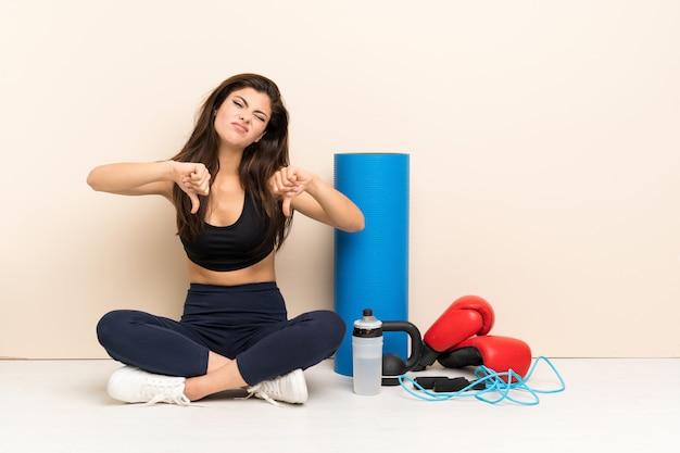 Menina do esporte adolescente sentada no chão, mostrando o polegar para baixo