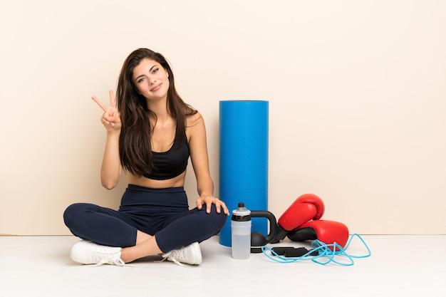Menina do esporte adolescente sentada no chão sorrindo e mostrando sinal de vitória