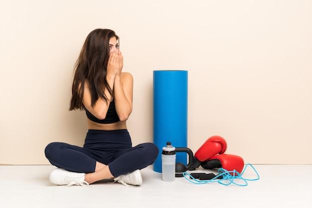 Menina do esporte adolescente sentado no chão cobrindo a boca e olhando para o lado