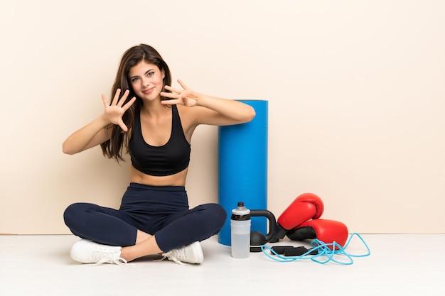 Menina do esporte adolescente sentado no chão contando nove com os dedos