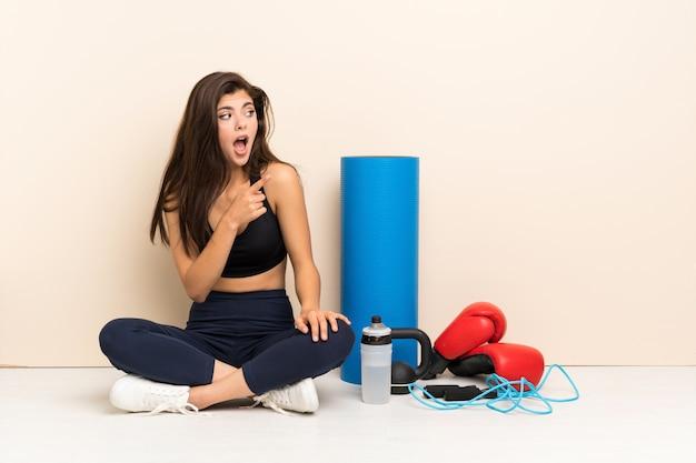 Menina do esporte adolescente sentado no chão surpreso e apontando o lado