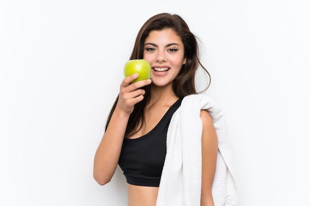 Menina do esporte adolescente sobre branco isolado com uma maçã