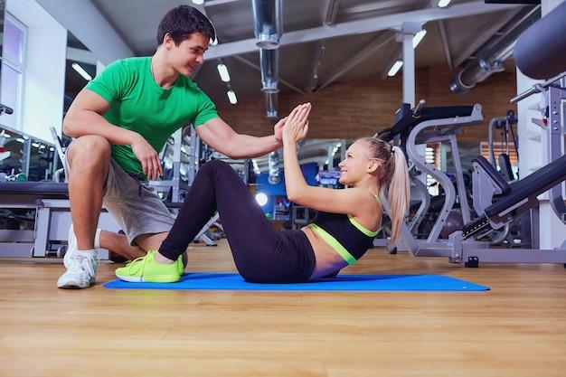 Menina do esporte fazendo exercícios abdominais com um homem treinador no chão do ginásio.