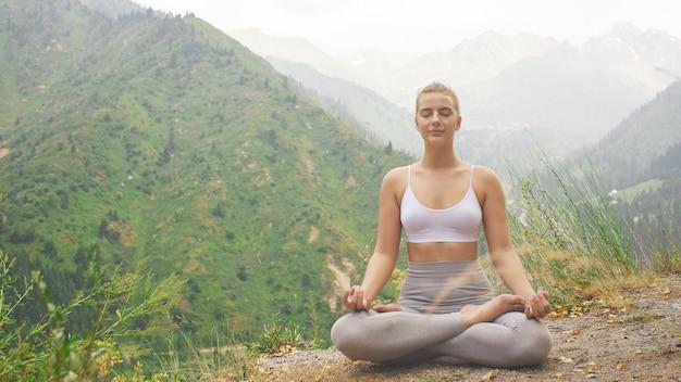Menina do esporte fazendo yoga na bela paisagem de montanhas.