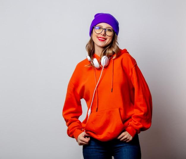 Menina do estilo com capuz laranja e chapéu roxo com fones de ouvido