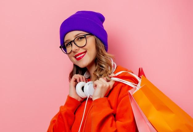 Menina do estilo com capuz laranja e chapéu roxo com sacos de compras na parede rosa