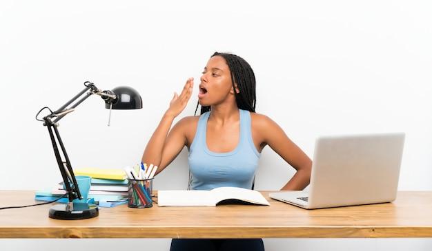 Menina do estudante adolescente americano africano com longos cabelos trançados em seu local de trabalho bocejando