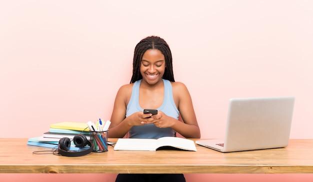Menina do estudante adolescente americano africano com longos cabelos trançados em seu local de trabalho enviando uma mensagem com o celular