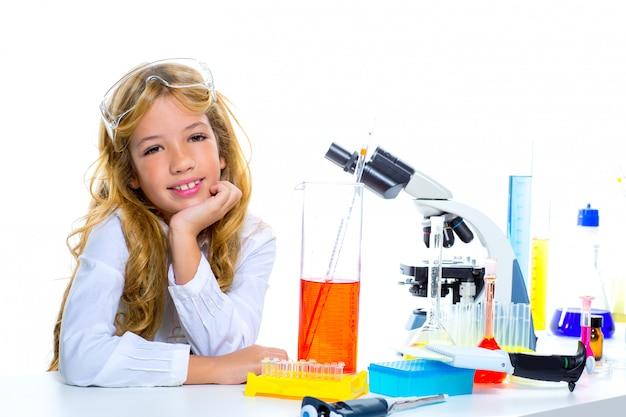 Menina do estudante das crianças no laboratório químico da criança