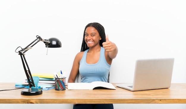 Menina do estudante do adolescente do americano africano com cabelo trançado longo em seu local de trabalho com polegares acima porque algo bom aconteceu