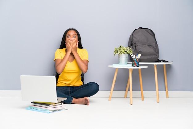 Menina do estudante do adolescente do americano africano com cabelo trançado longo que senta-se no assoalho com expressão facial da surpresa
