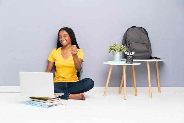 Menina do estudante do adolescente do americano africano com cabelo trançado longo que senta-se no assoalho que convida para vir