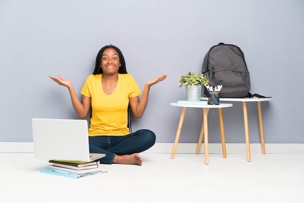 Menina do estudante do adolescente do americano africano com cabelo trançado longo que senta-se no assoalho que tem dúvidas com confundir a expressão da face
