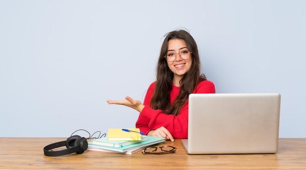 Menina do estudante do adolescente que estuda em uma tabela que apresenta uma ideia ao olhar de sorriso para